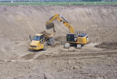 Excavator dumping dirt into a dump truck